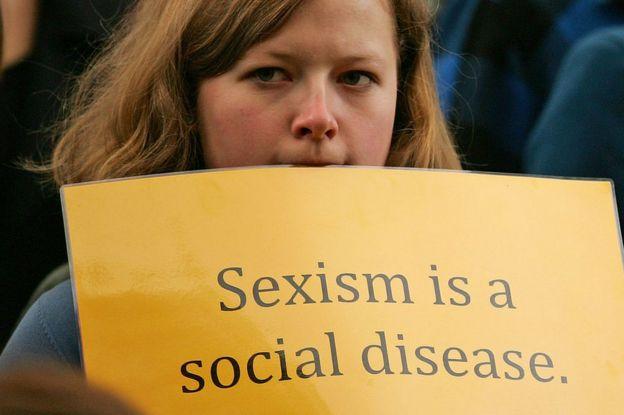Mujer sostiene una pancarta que denuncia el sexismo.