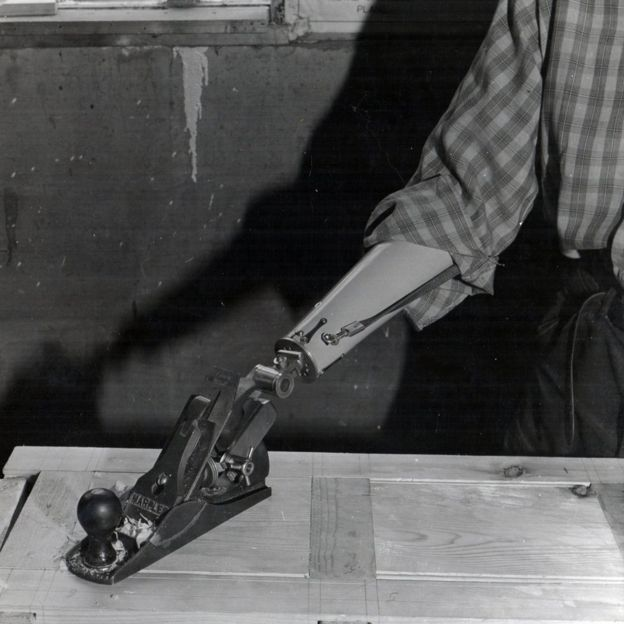 A man with a wood plane attached to his arm