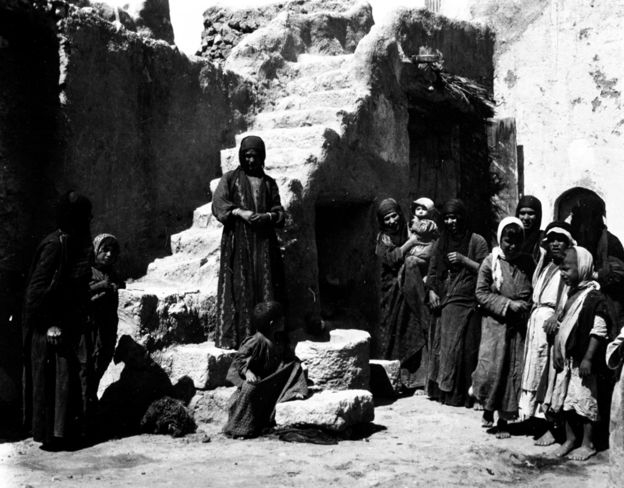 Photograph from Gertrude Bell Archive: People standing outside a house in a courtyard in Palmyra
