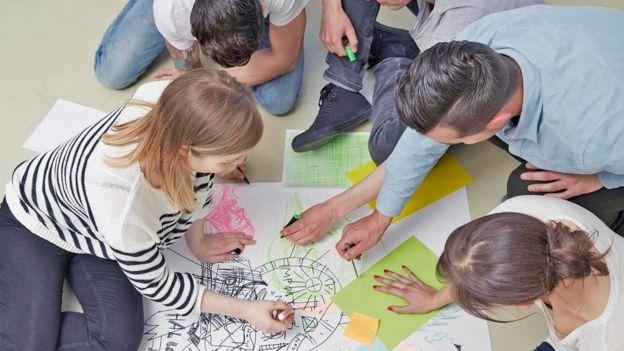 Adultos y niños coloreando en el piso