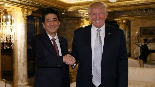 Shinzo Abe shakes hands with Donald Trump