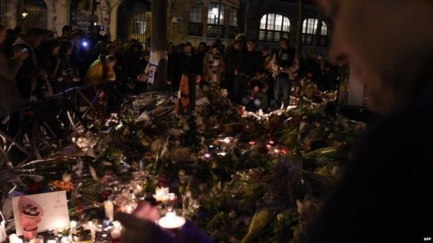 People gather at a makeshift memorial site on November 15, 2015, outside the La Belle Equipe cafe, rue de Charonne,