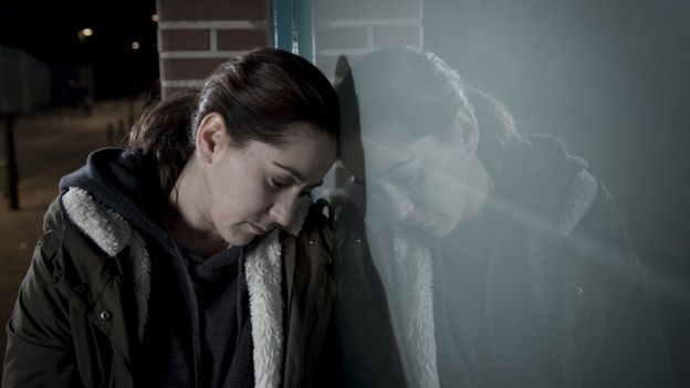 mujer apoya su rostro en una ventana con visible pesadumbre.