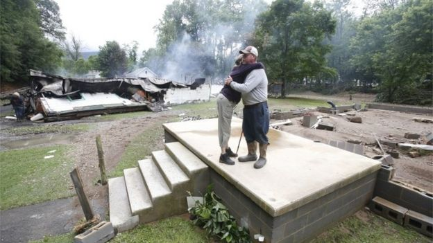 Jimmy Scott gets a hug from Anna May Watson, left, as they clean up from severe flooding in West Virginia.