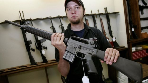 Un vendedor muestra un fusil AR15