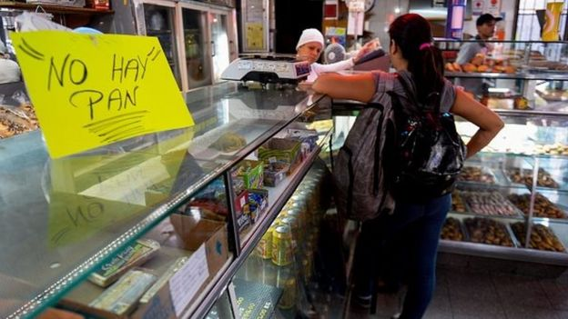 A woman waits at a bakery displaying a sign reading