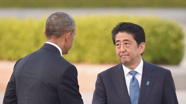 El presidente de EE.UU. Barack Obama (izq.) le da la mano al primer ministro de Japón, Shinzo Abe, durante su visita al Monumento de la Paz en Hiroshima, el 27 de mayo, de 2016