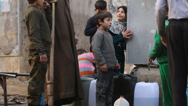 أطفال ينتظرون الحصول على المياه في حلب