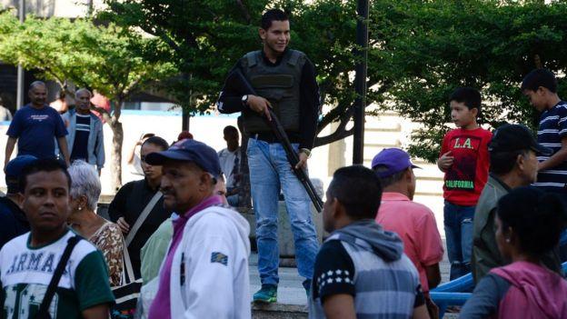 Un agente armado frente a una fila en Caracas