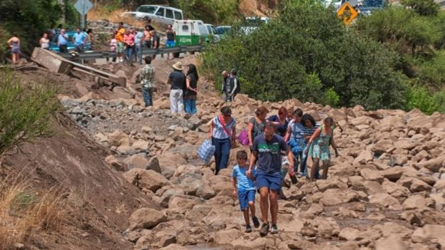 People walk along a damage road after a flood near Santiago, Chile February 26, 2017.