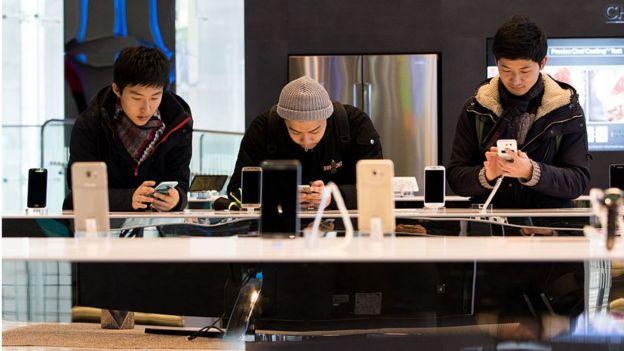 Tres jóvenes probando distintos modelos de celulares