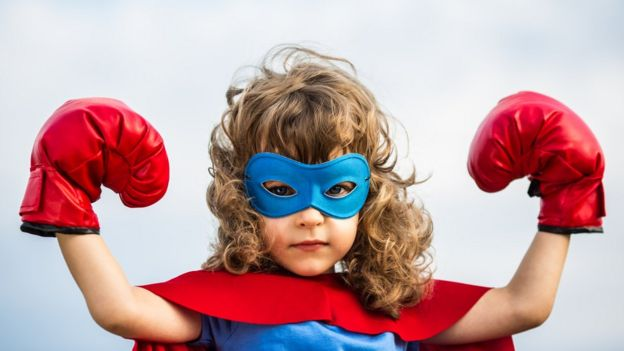 Niña con traje de Superman y guantes de boxeo.