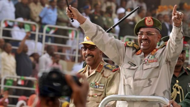 Sudan's President Omar al-Bashir (R) and Defence Minister Abdelrahim Mohamed Hussein (L) greet the crowd during a visit to the Popular Defence Forces in Khartoum on March 3, 2012.