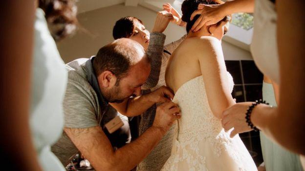 El refugiado sirio Ibrahim Halil Dudu repara el cierre del vestido de boda de Jo Du.