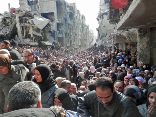 Residents wait in line to receive food aid distributed in the Yarmouk refugee camp on January 31, 2014 in Damascus, Syria