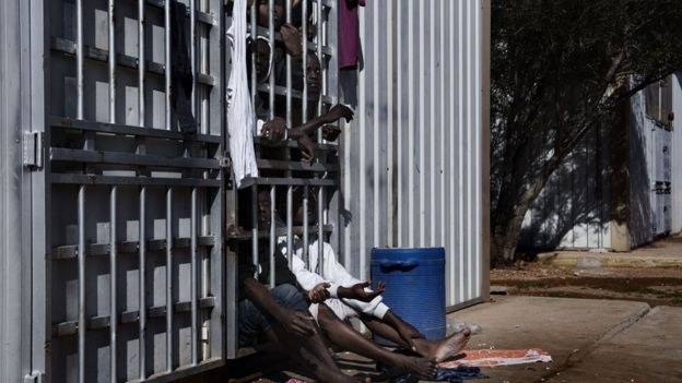 Migrants behind bars in a detention centre in Libya