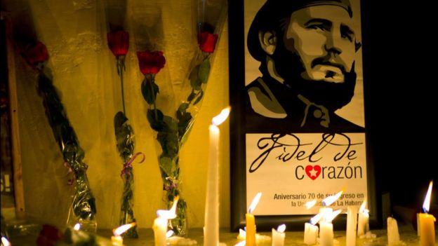 Velas y flores frente a un retrato de Fidel Castro en La Habana