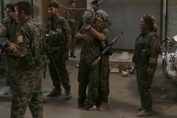 SDF fighters celebrate inside Manbij, Syria, 10 August