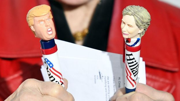 A woman holds pens in the shape of Donald Trump and Hillary Clinton