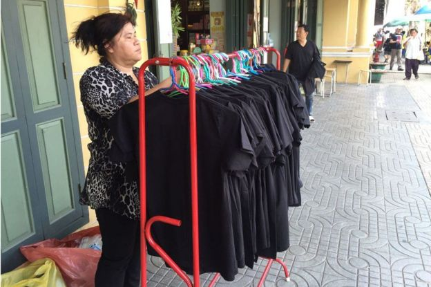 Una mujer tailandesa junto a un conjunto de camisetas negras