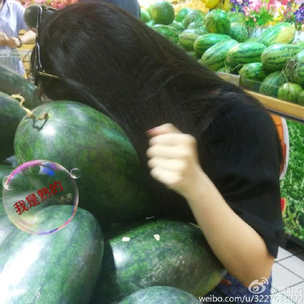 Photo of a woman leaning over a lot of watermelons. Her hair covers her face as she listens to the fruit.