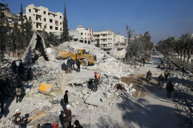 Syrian men and rescue workers search for survivors after air strikes in rebel-held city of Idlib on 7 February 2017