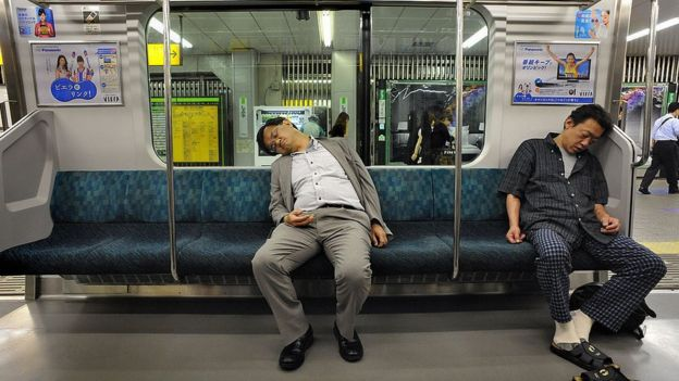 Two sleeping Japanese commuters on a train in Tokyo