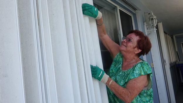 Señora poniendo contraventanas para proteger su casa