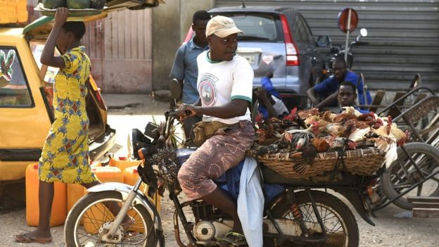 A man carries chickens on his motorcycle at a market in Cotonou, Guinea - 2015