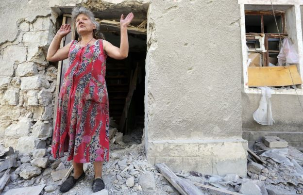 A woman reacts in front of her house destroyed as a result of shelling between Ukrainian forces and pro-Russian separatists on 10 August 2015 in Golmovsky village, Donetsk region