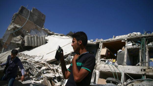 Homem tira foto dos destroços resultantes de um ataque em Damasco com seu celular