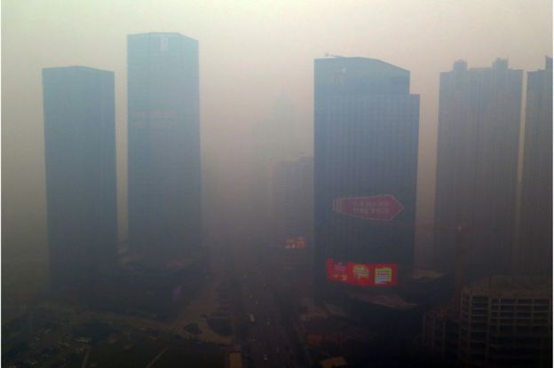 This picture taken on 8 November 2015 shows a residential block shrouded in smog in Shenyang, Liaoning province