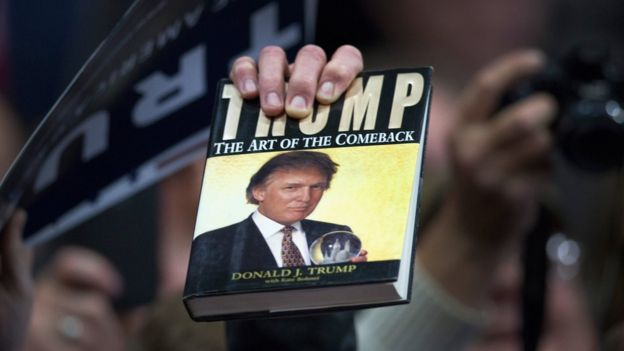 Man holds up a book by Donald J. Trump at a campaign rally.