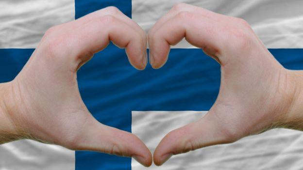 Bandera y gesto de corazón.