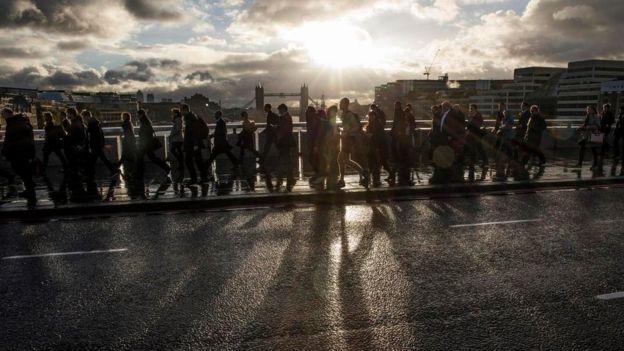 Trabajadores que cruzan a pie el Puente de la Torre de Londres, camino al trabajo