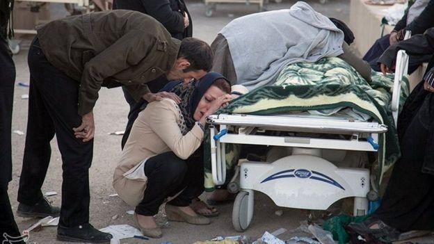 A woman reacts next to a dead body following an earthquake in Sarpol-e Zahab county in Kermanshah, Iran November 13, 2017