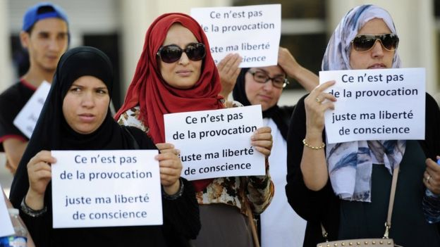 Women hold signs reading 'Is it not a provocation, just my freedom of conscience' during a 'headscarf march' organized by the Collective against Islamophobia 'Respect Equality Dignity' on 3 September 2016 in Avignon, southern France