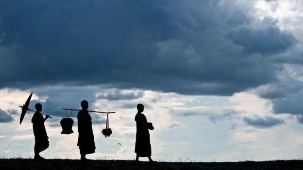 Tres tibetanos caminando contra un fondo de nubes, en contraluz