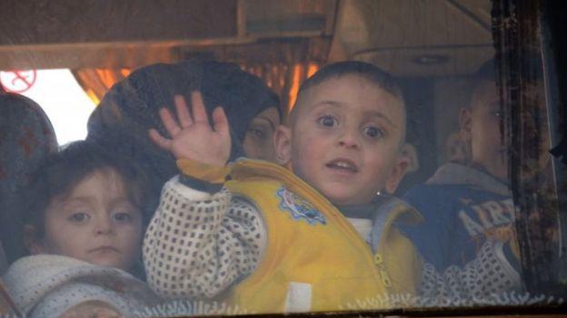 أطفال ونساء يستقلون الحافلات المغادرة لحمص