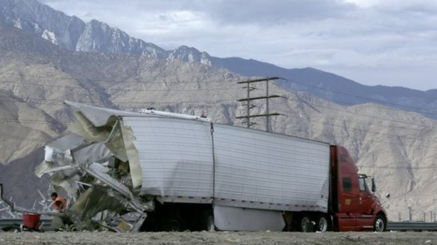 Workers and law enforcement personnel inspect a truck that was in collision with a tour bus on Interstate 10 near Palm Springs (23 October 2016)
