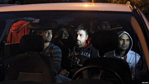 Migrants sit in a car, on their way through Austria