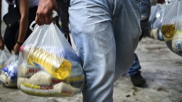 Una persona que lleva una bolsa de comida