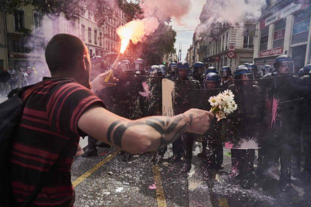 A protester faces police with a torch and a bouquet of flowers in Lyon, 26 May