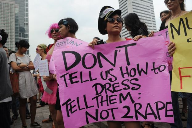 An Indonesian woman holds up a pink sign with black lettering on it, reading