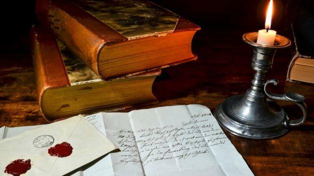 Libros, velas y documentos antiguos.
