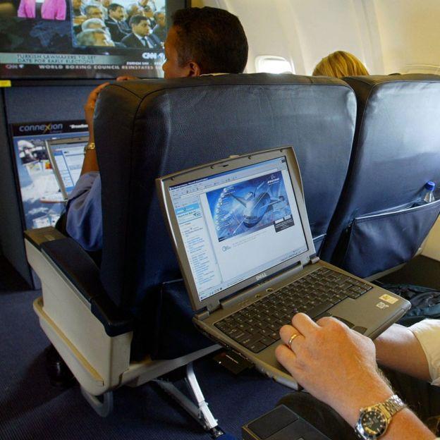 Hombre con una laptop en un avión.
