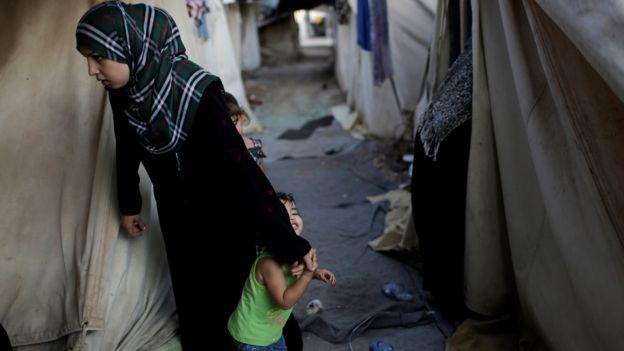 Mulher síria refugiada e seus filhos em campo de refugiados em Atenas, Grécia