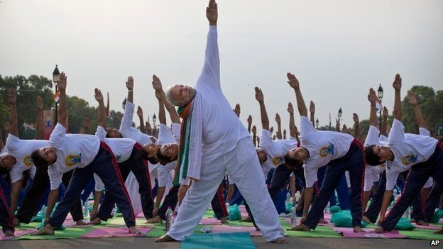 Indian Prime Minister Narednra Modi performs yoga along with thousands of Indians on Rajpath, in New Delhi, India, Sunday, June 21, 2015.