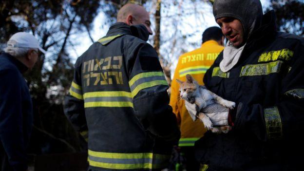 An Israeli fireman holds a cat