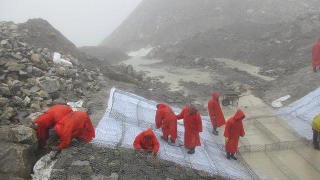Trabajadores en Nepal colocando una malla en la ladera de una montaña para evitar el deslizamiento de rocas